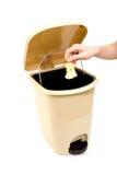 Hand die appel in afval werpt Stock Foto's