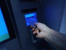Hand die ATM-kaart opnemen in bankmachine om geld terug te trekken Stock Afbeeldingen