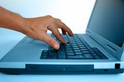 Hand, die auf einem Laptop schreibt Lizenzfreie Stockbilder