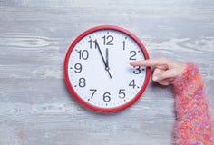 Hand, die auf einer Uhr poiting ist Stockfotos