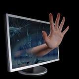 Hand, die aus ein Computerüberwachungsgerät herauskommt. Lizenzfreie Stockfotografie