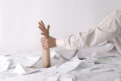 Hand, die aus Schreibtisch voll der Papiere heraus stikking ist lizenzfreie stockfotografie