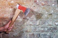 Hand, die Axt gegen Backsteinmauer hält Lizenzfreie Stockfotografie