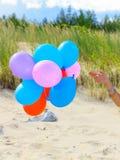Hand, die Ballone auf Strand im Freien hält Lizenzfreies Stockfoto