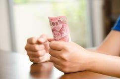 Hand, die Banknote des thailändischen Baht 100 hält Lizenzfreie Stockfotos