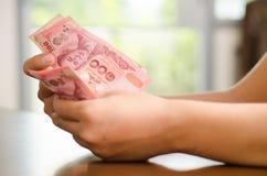 Hand, die Banknote des thailändischen Baht 100 hält Stockfoto