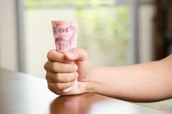 Hand, die Banknote des thailändischen Baht 100 hält Stockbilder
