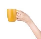 Hand, die Becher lokalisiert auf Weiß hält. Lizenzfreie Stockfotos