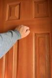 Hand die bij de deur klopt. stock fotografie