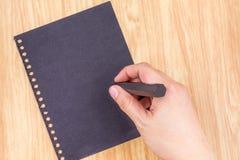 Hand die bij zwarte paperl op houten lijstbovenkant schrijven, Zaken Brainst royalty-vrije stock foto's