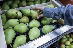 Hand, die Birne im Supermarkt emporragt stockfotografie