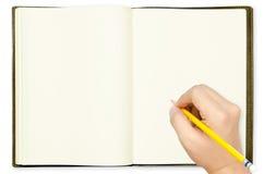 Hand, die Bleistift auf leerem Anmerkungsbuch hält Lizenzfreie Stockfotos