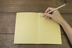 Hand, die Bleistift auf Notizbuch hält stockbilder