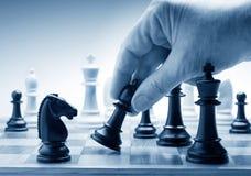 Hand, die an Bord eine Schachfigur bewegt Stockbild