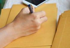 Hand die buitenadres op bruine envelop schrijven stock afbeelding