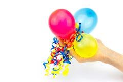 Hand, die bunte Ballone mit Bändern gibt Stockfotos