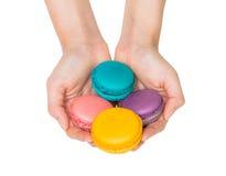 Hand, die bunte macarons hält Lizenzfreie Stockbilder
