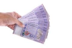 Hand, die ca. malaysisches Ringgit 100 hält Lizenzfreie Stockfotos