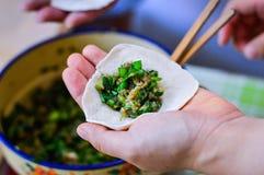 Hand, die chinesische Mehlkloß-Haut mit Schweinefleisch-Schnittlauch-Füllungen hält Stockbild