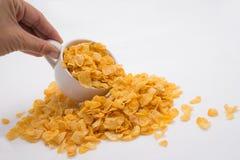 Hand, die Corn Flakes aus kleiner Schale heraus verschüttet Lizenzfreies Stockbild