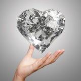Hand die 3d vorm van het diamanthart houden Stock Afbeelding