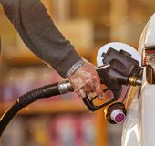 Hand, die das Auto mit Kraftstoff wieder füllt stockbild