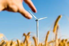 Hand, die das Blatt einer Windkraftanlage ergreift stockbild