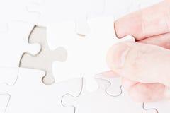 Hand, die das letzte Puzzlespielstück setzt stockbild