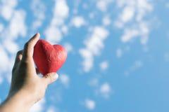 Hand, die das rote dekorative Herz gegen den blauen Himmel hält stockfotografie