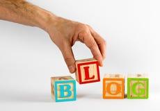 Hand, die das Wort-Blog mit Blöcken buchstabiert Stockbild