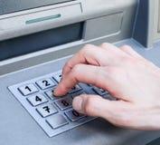 Hand die de aantallen van de SPELD op de bankmachine van ATM ingaat Stock Afbeelding