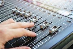 Hand die de audioknopen, faders en de schuiven van de mixerconsole aanpassen Stock Afbeeldingen