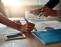 Hand die de bedrijfs van mensen de grafiek in het bureau analyseren stock fotografie