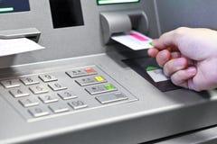 Hand die de creditcard van ATM opnemen in terug te trekken bankmachine zich mon stock foto