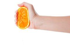 Hand die de helft van sinaasappel drukt Stock Afbeelding