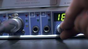Hand die de knopen op een functionerende audioversterker in een geluidsopnamestudio aanpassen stock footage