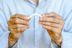 Hand die de laatste sigaret breken ophouden rokend Stock Fotografie