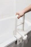 Hand die de leuning in de badkamers houden stock afbeeldingen
