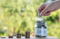 Hand die de stapel van geldmuntstukken groeien zetten, die geld voor doelconcept besparen royalty-vrije stock afbeeldingen