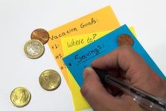 Hand die de uitgaven neerschrijft het berekenen vakantiegeld pen Kleurrijke Nota's euro pence stock afbeelding