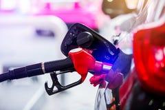 Hand die de witte pick-up met brandstof opnieuw vullen bij het benzinestation stock foto