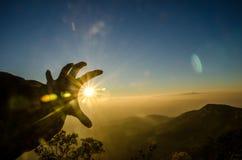 Hand die de zon op Berg houden Royalty-vrije Stock Foto's