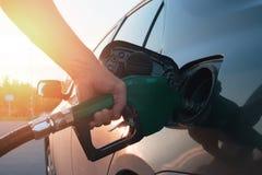 Hand, die den Brennstoff in das Auto führt Stockbild