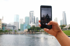 Hand, die den Handy macht Stadtbild-Foto hält Stockbilder