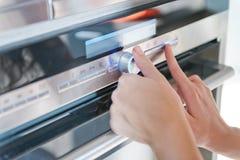 Hand, die den Timer-Griff auf Ofen bewegt Stockbild