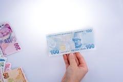 Hand, die in der Hand Turksh-Lirabanknote hält Stockfotos