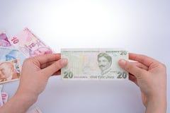 Hand, die in der Hand Turksh-Lirabanknote hält Stockfoto