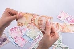 Hand, die in der Hand Turksh-Lirabanknote hält Stockbilder