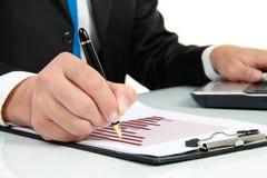 Hand, die am Diagramm auf Finanzreport überprüft Lizenzfreie Stockfotografie