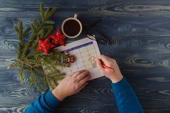 Hand die die 25 December in een kalender richten door Kerstmis wordt omringd Stock Fotografie